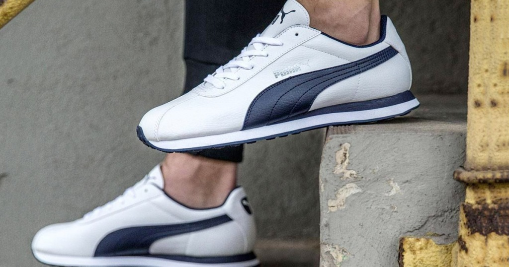 person on a step wearing a pair of white and navy blue puma sneakers