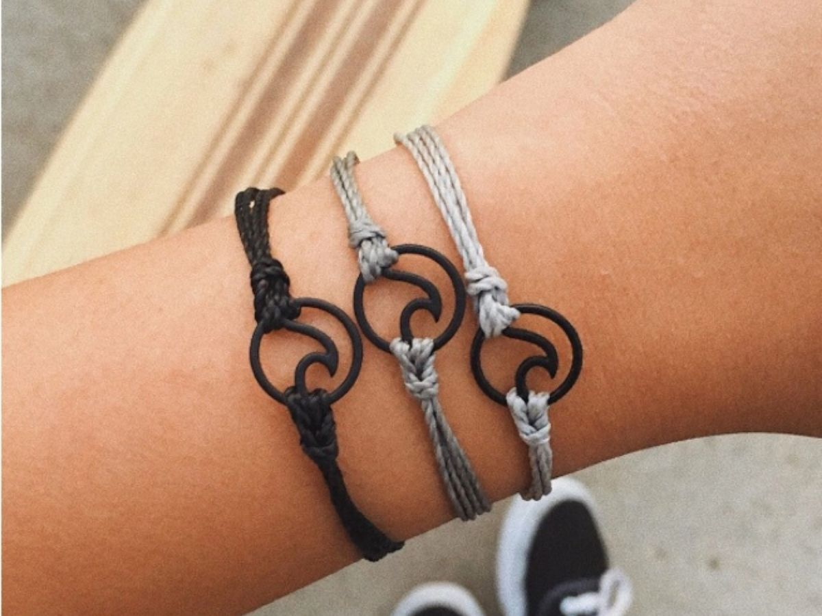 womans wrist with 3 bracelets with wave charm