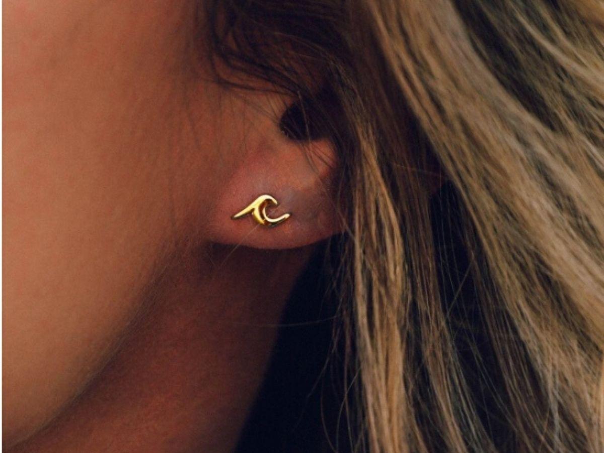 woman wearing gold tone wave earrings