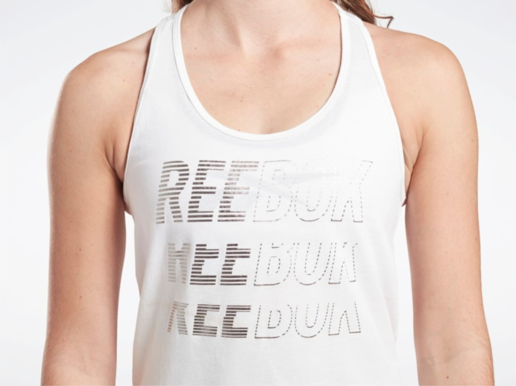 woman in white graphic logo tank top