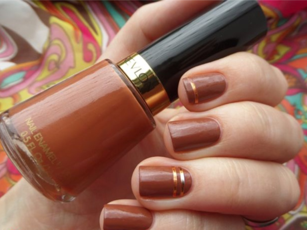 nail polish bottle and nails painted light brown