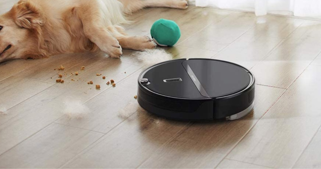 robot vacuum on wood floor vacuuming by dog