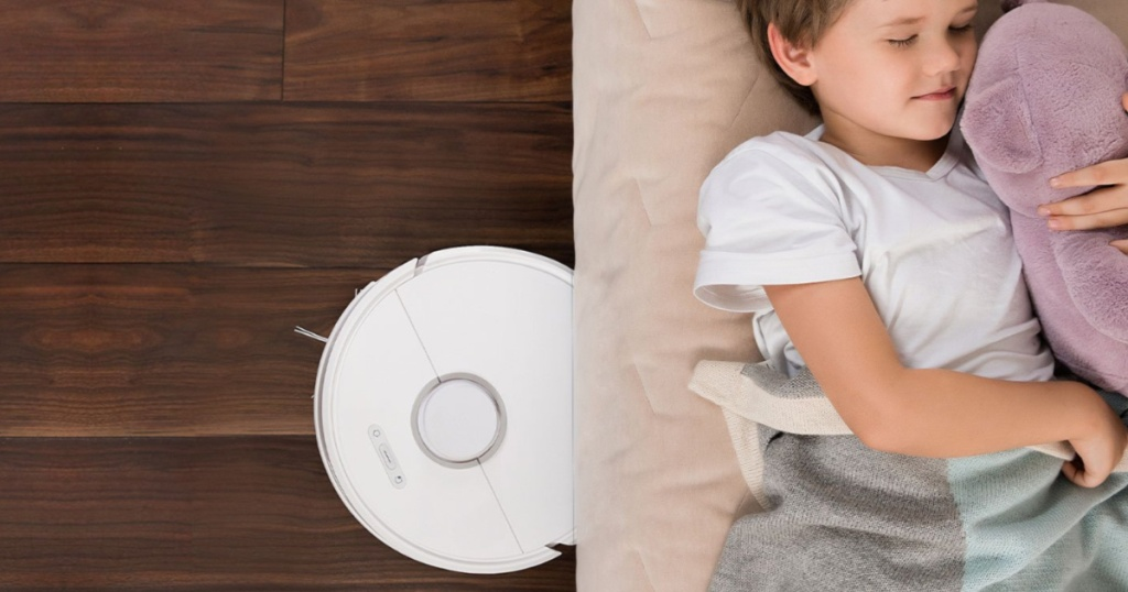 Roborock S6 Robot Vacuum under a couch where a child is sleeping