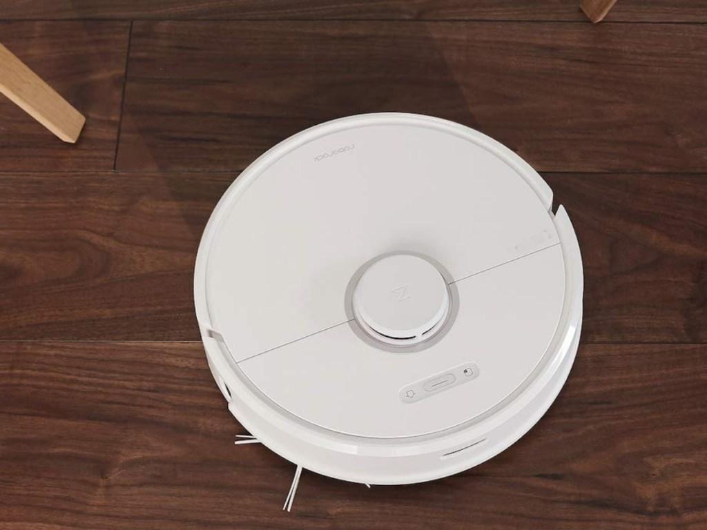 white robot vacuum on a brown hardwood floor