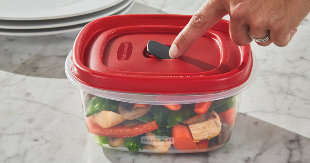 finger pressing on food container red vented lid on counter next to stack of three white plates