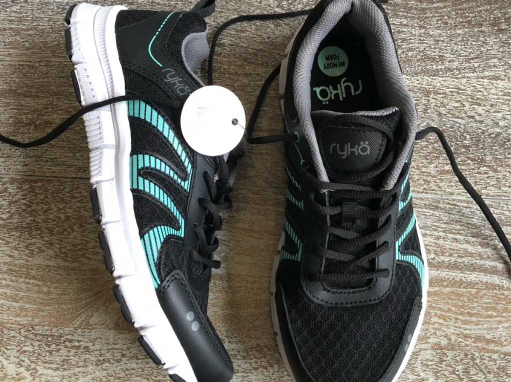 black and blue women's running shoes on floor