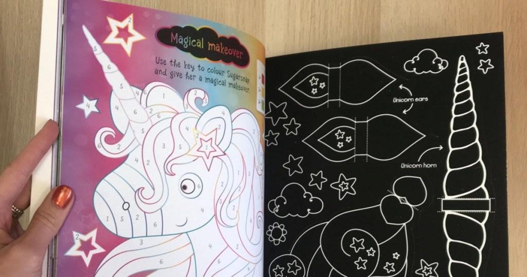 hand holding open scratch unicorn-themed unicorn book