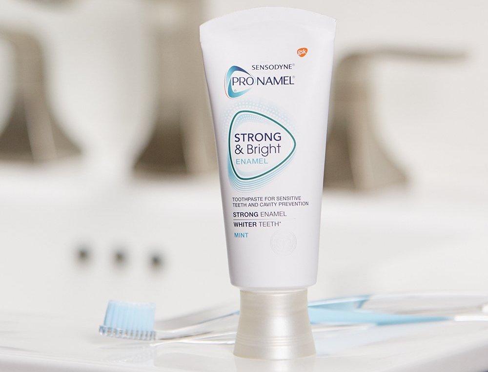 Sensodyne toothpaste next to toothbrush on bathroom counter