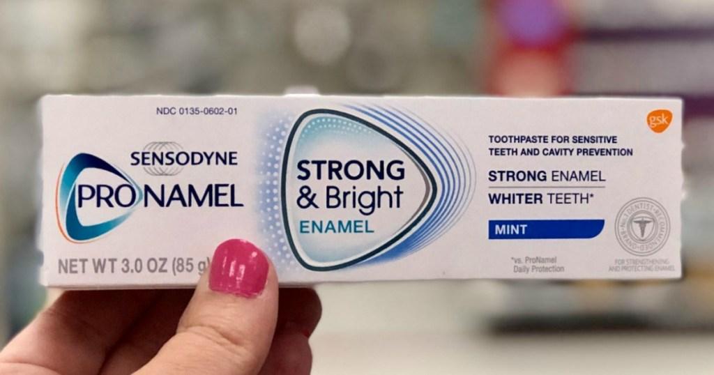 hand holding box of Sensodyne toothpaste
