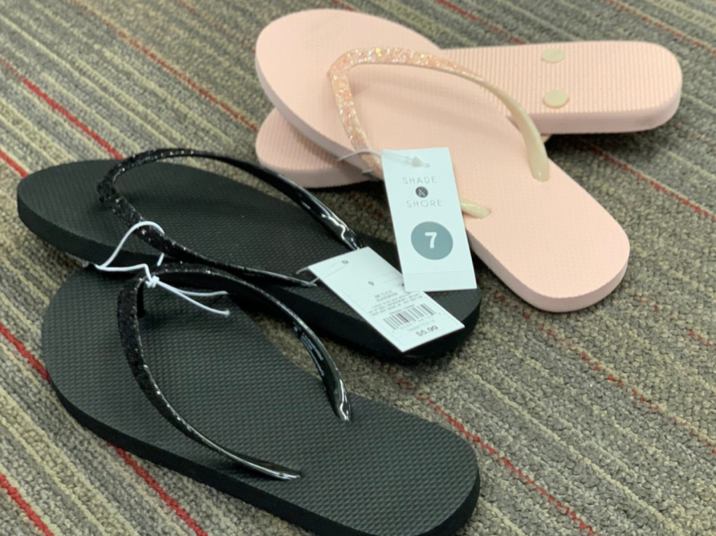 women's pink and black sandals on floor in store