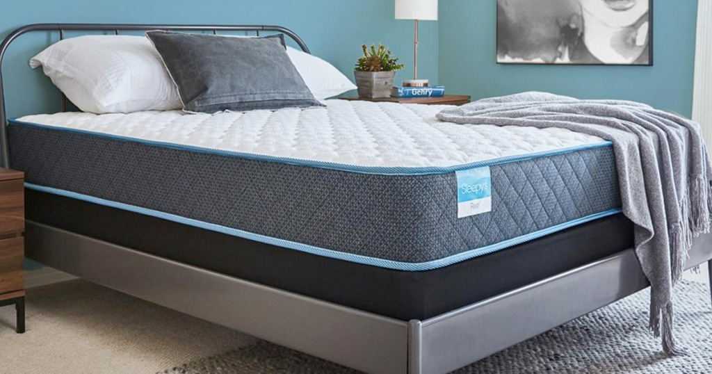 grey and white mattress on a grey metal bed frame in a blue bedroom