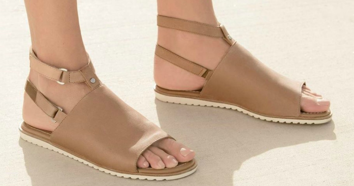 person wearing pair of tan sandals