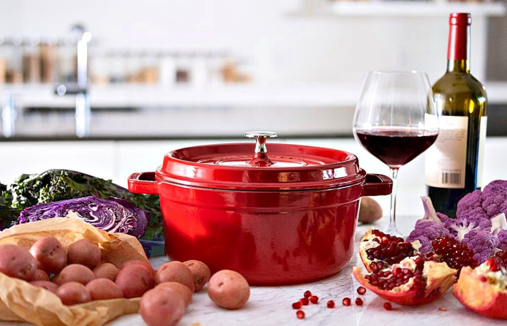 Staub 4-Quart Round Cocotte red on counter with wine and vegetables