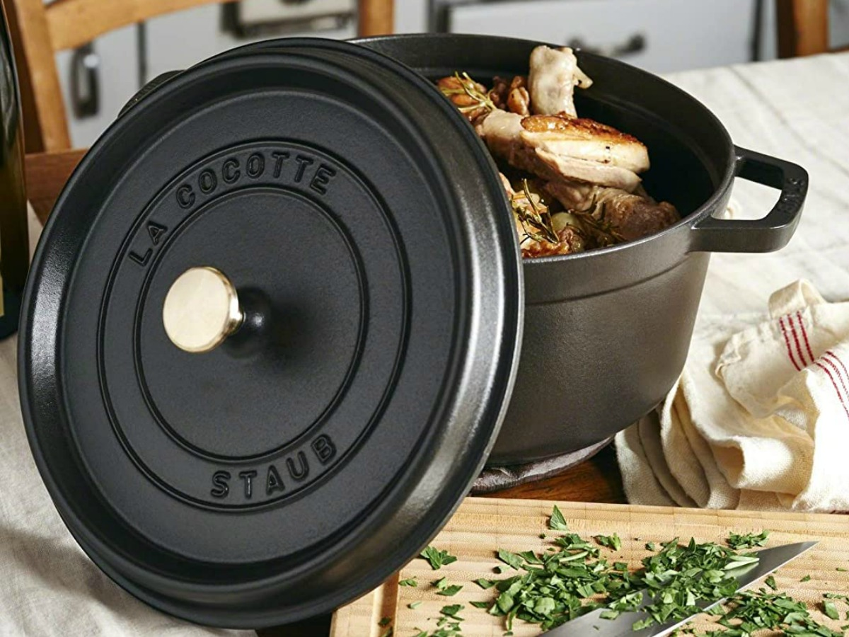 Black cast iron cocette with chicken quarters and herbs inside