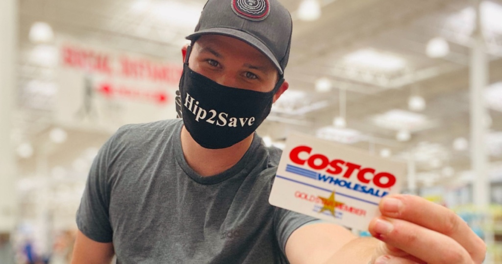 man wearing face mask in store holding Costco membership card