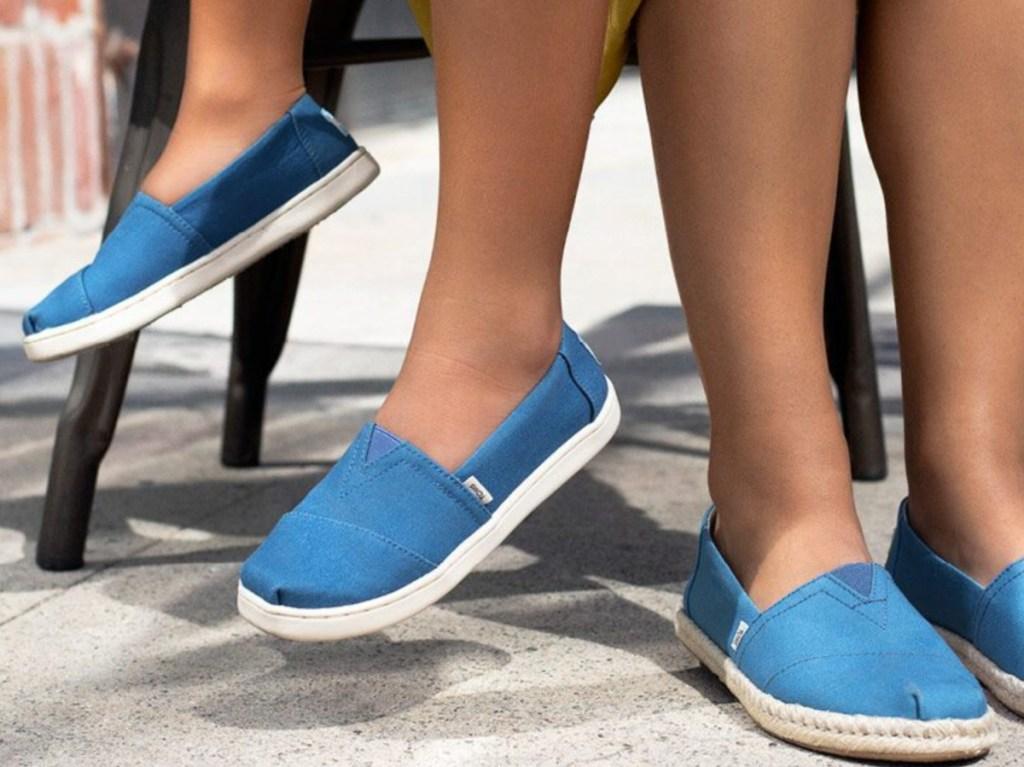 two kids wearing blue slip ons outside