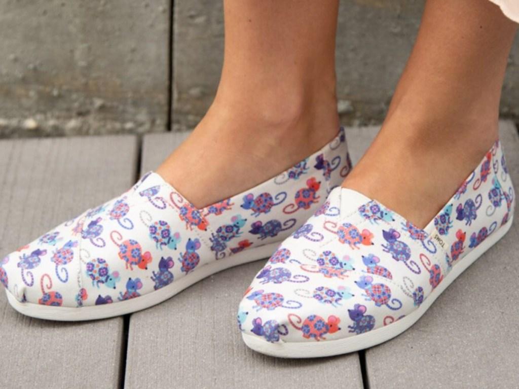 feet in white rat slip on shoes