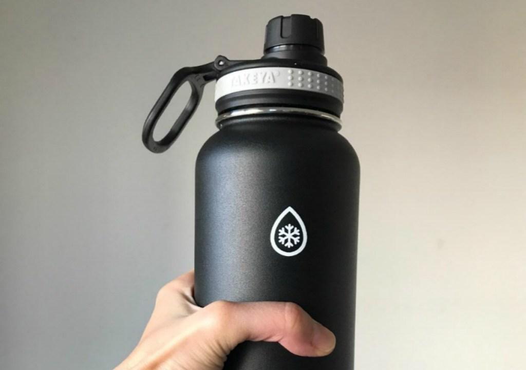 woman holding black water bottle
