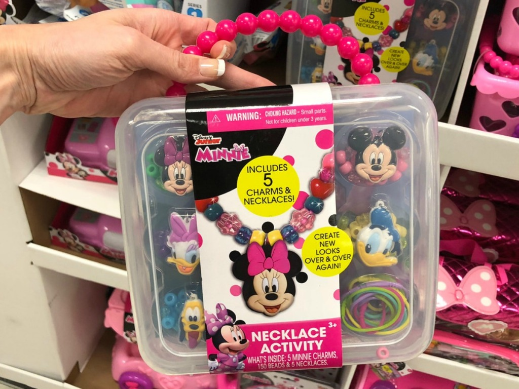 hand holding up Disney minnie mouse toy that has necklace building beads in it