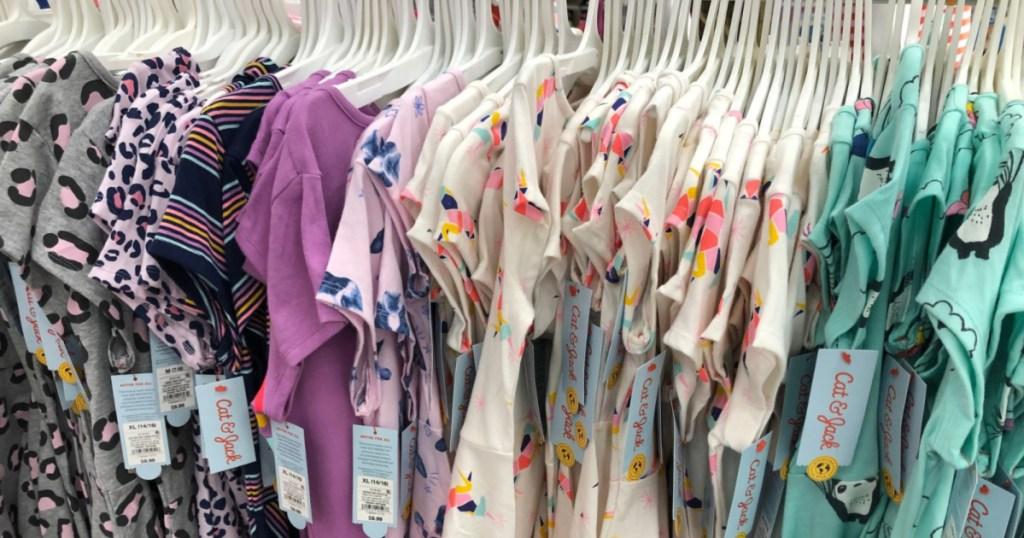 various girls dresses hanging on store rack
