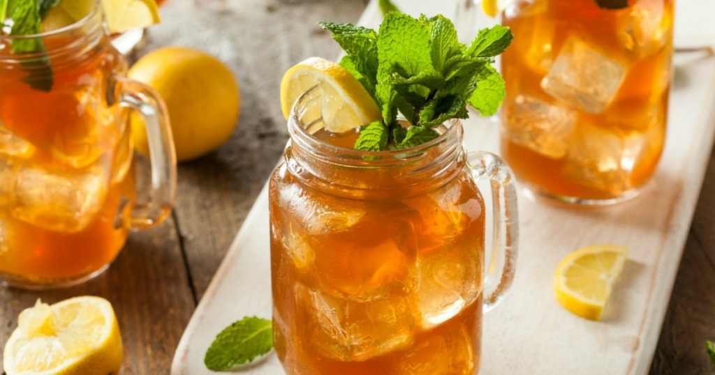 iced tea with mint sprigs and lemon wedges in mason jars