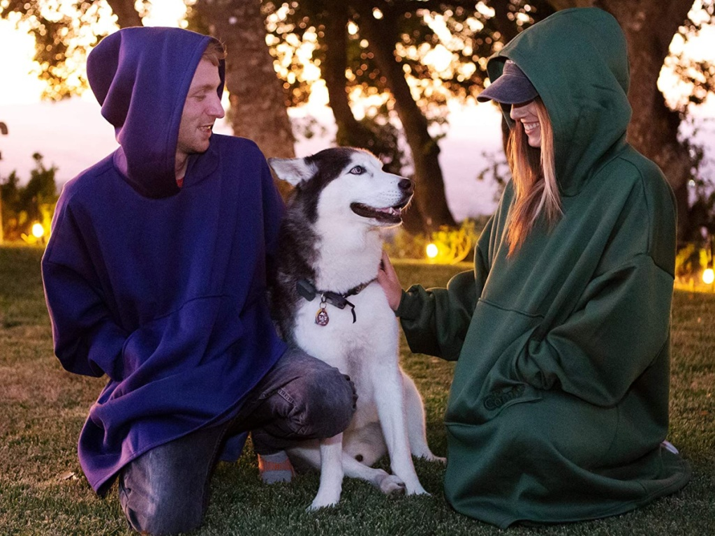 man and woman and dog sitting in blanket sweatshirts outdoors