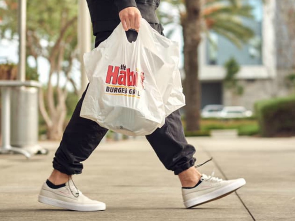 Person carrying The Habit Burger Takeout Bags