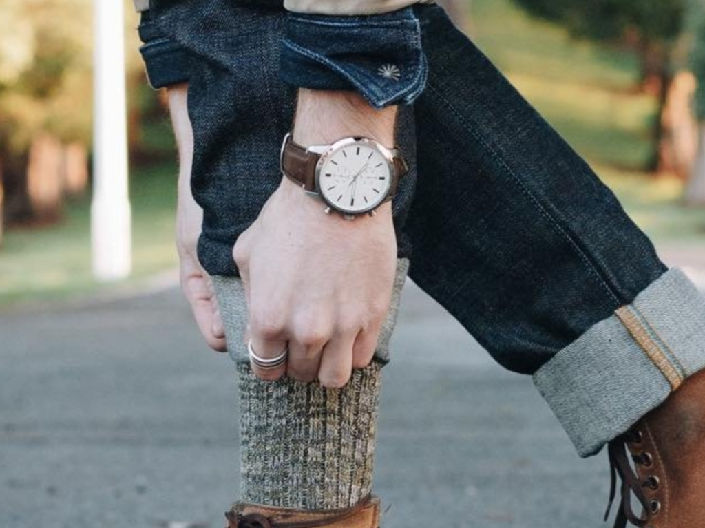 man pulling up sock outside with brown leather watch on wrist