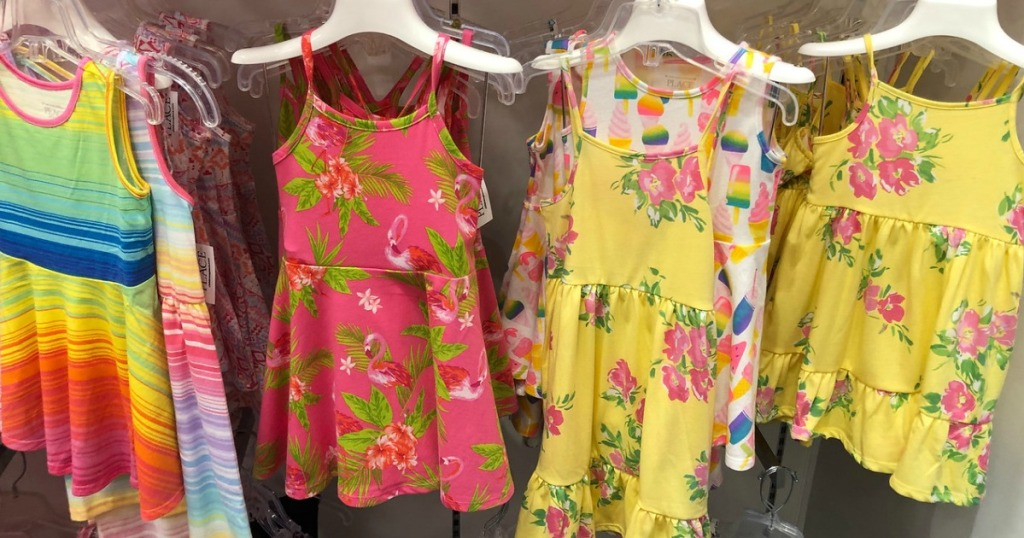 girls striped and floral dresses hanging in a store