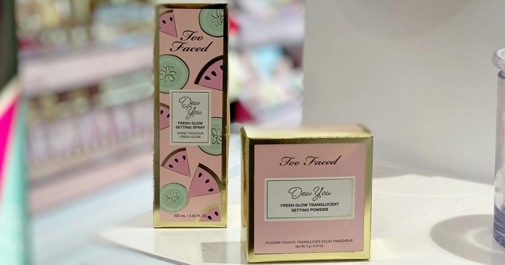 packages of too faced tutti fruity dew you setting powder and setting spray on white shelf