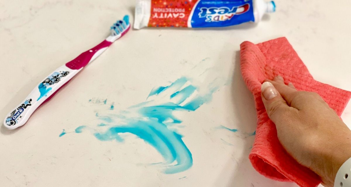 Hand using a Swedish Dishcloth to clean up a toothpaste mess in the bathroom