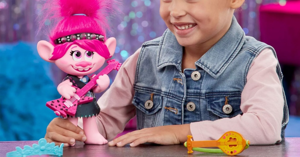 girl playing with pink trolls doll with pink guitar