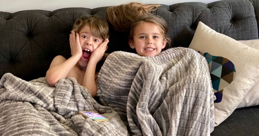 Two kids sitting on the couch under a blanket smiling