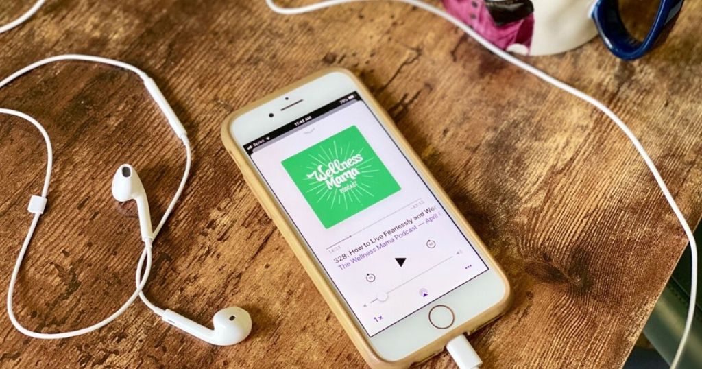 Headphones and an iphone displaying a podcast sitting on a desk