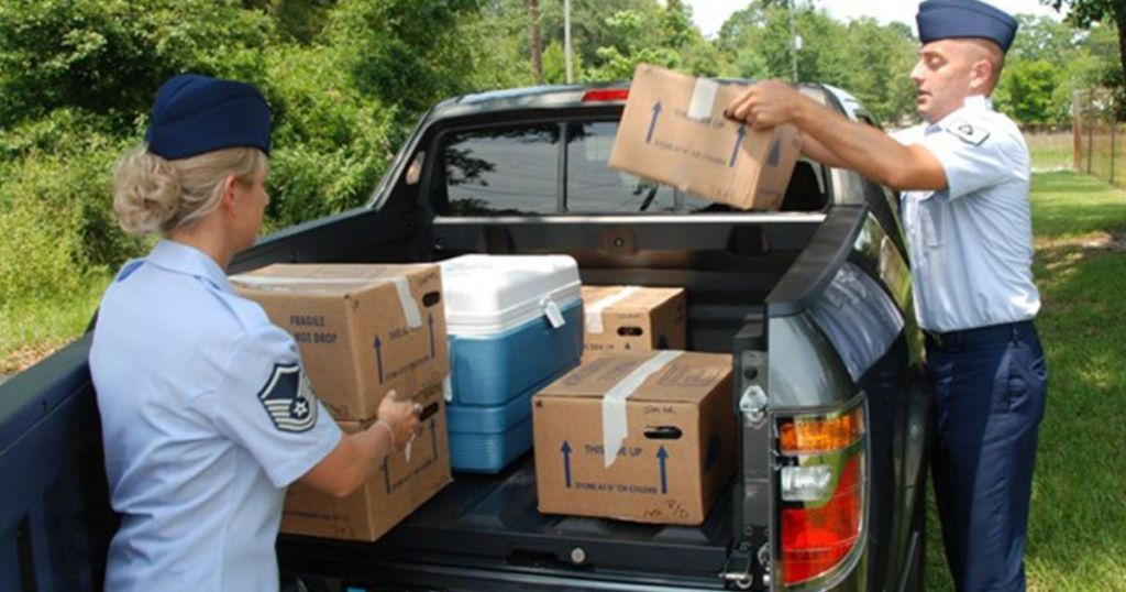 Men in Air Force uniforms placing boxes of food in the back of a truck for delivery