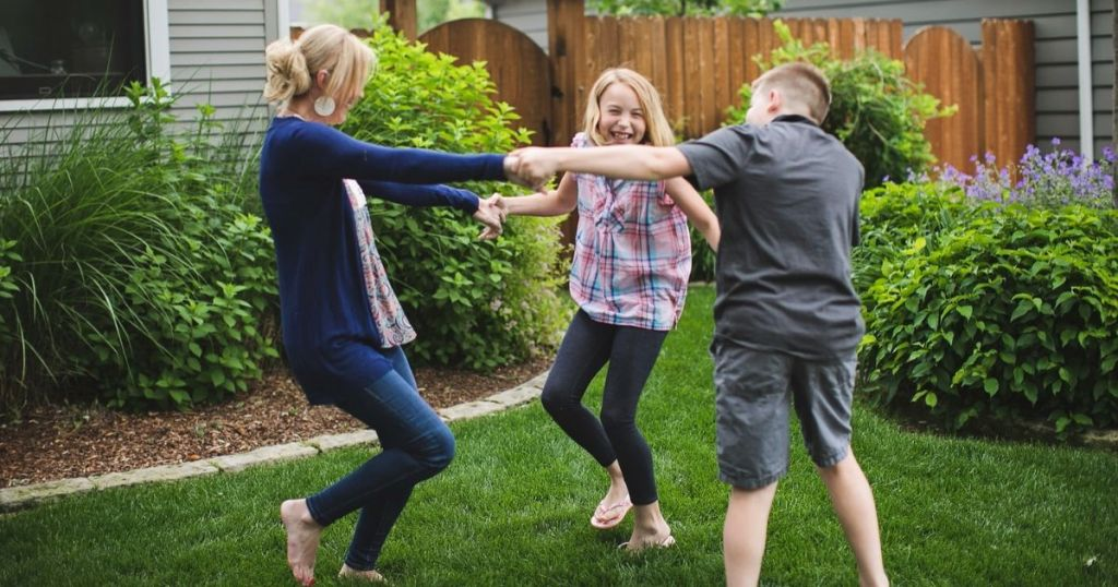 Mom dancing with her kids in the backyard