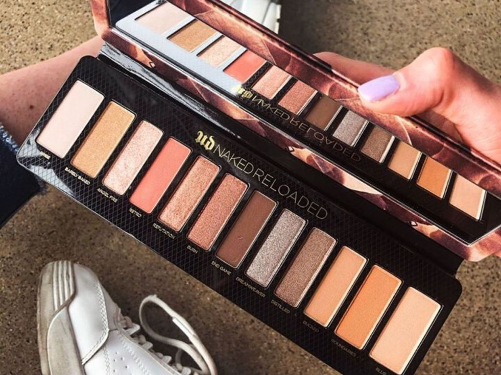 womans hand holding 12 shade eyeshadow palette open sitting on the floor