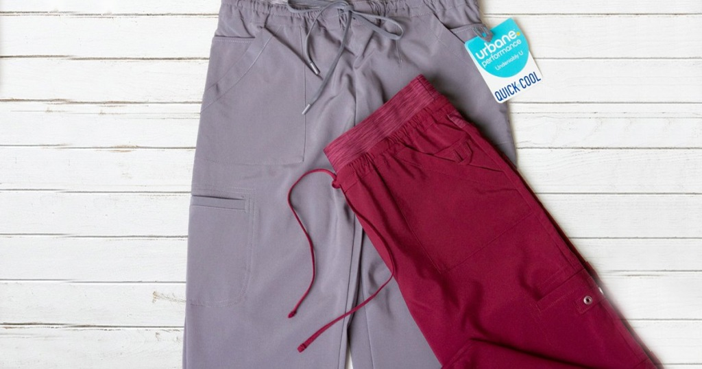 grey and maroon colored scrub pants on white wood background