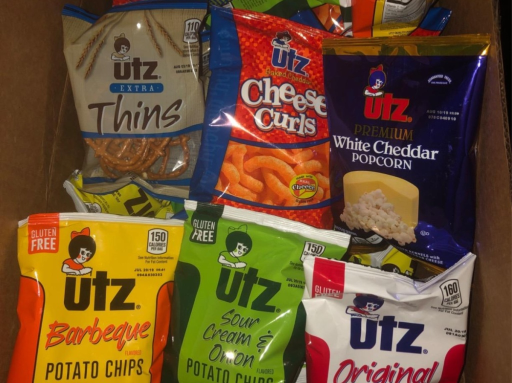 various bags of chips and other snacks in cardboard box