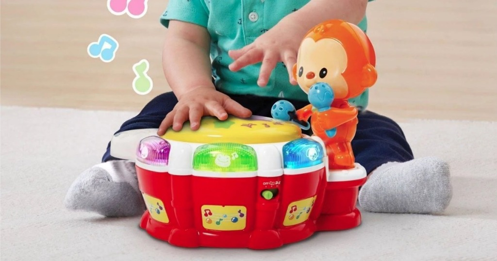 baby on floor with VTech Baby Beats Monkey Drum