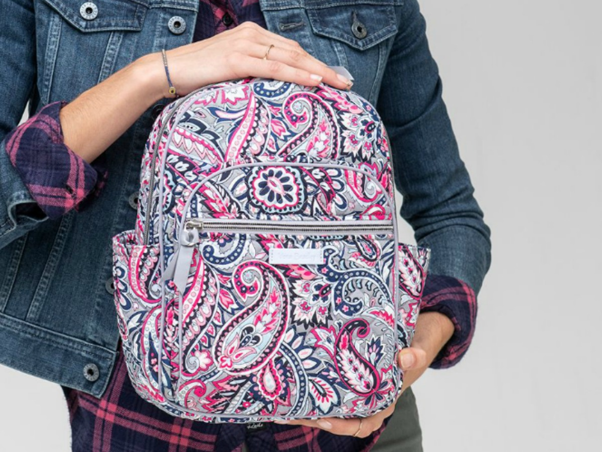 Woman wearing a denim jacket and holding a paisley print backpack