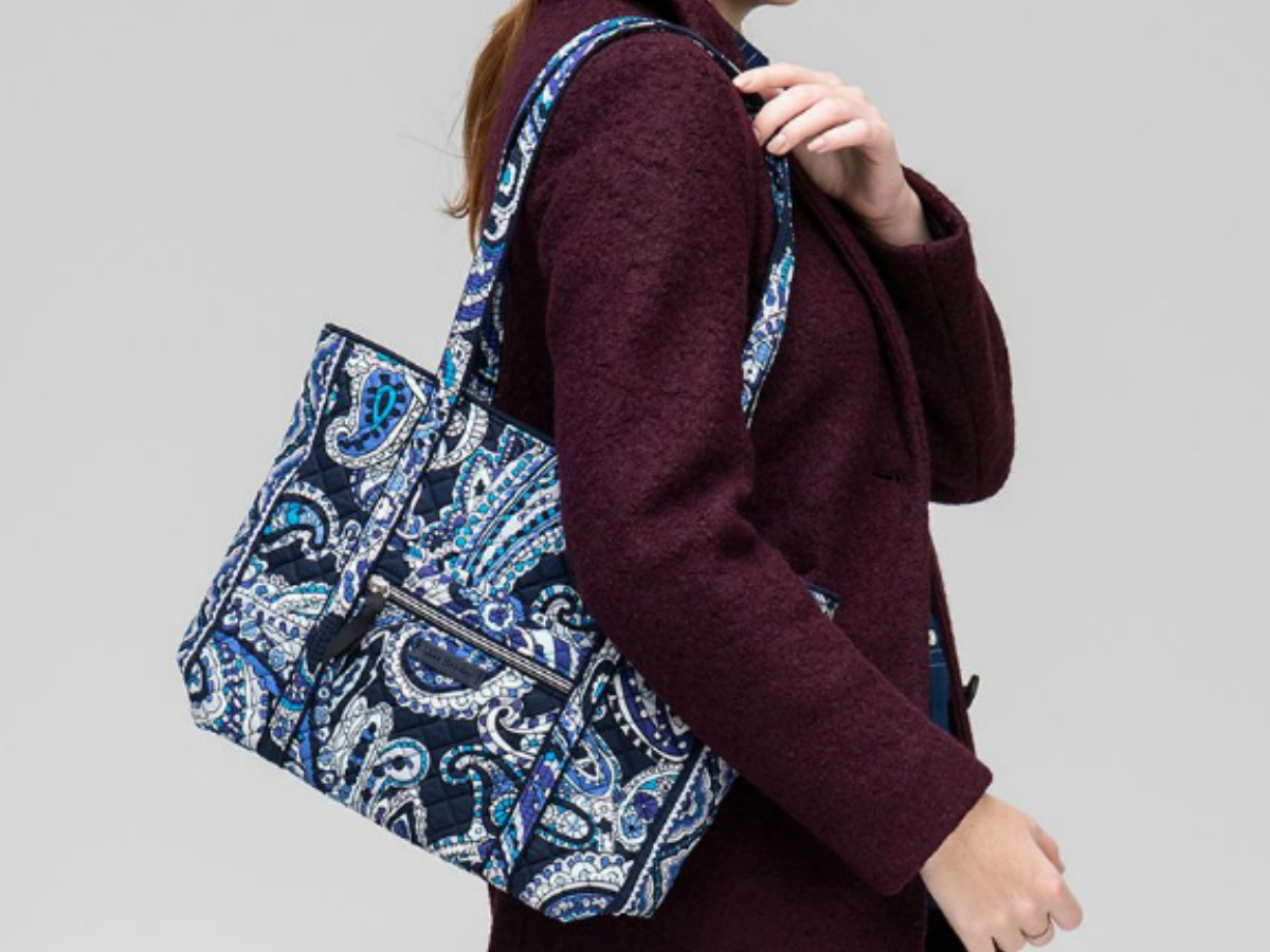 Woman wearing a jacket and a paisley print tote bag