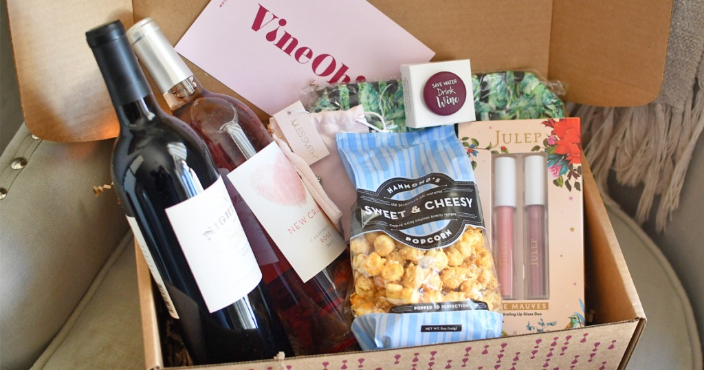 box with two bottles of wine, popcorn, cosmetic bag, lip glosses, wine cap, and necklace