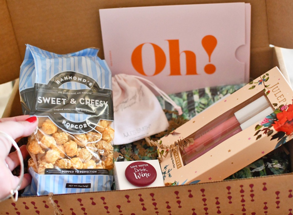 box with popcorn, julep lip gloss, necklace, wine cap, and cosmetic bag
