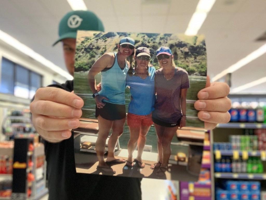 Pria memegang foto besar tiga wanita di luar dalam walgreens