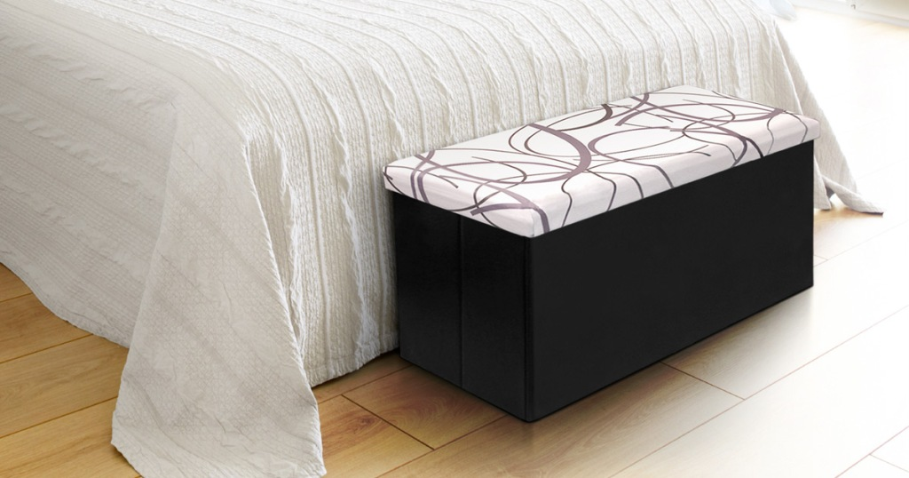 storage ottoman at bottom of bed, white top with black swirls and faux leather bottom