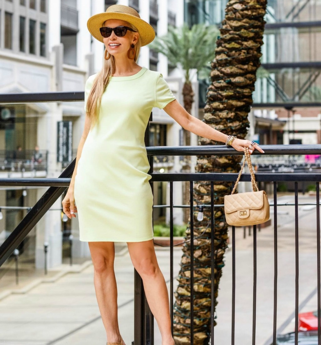 woman in short-sleeved lime green dress posing with a small purse