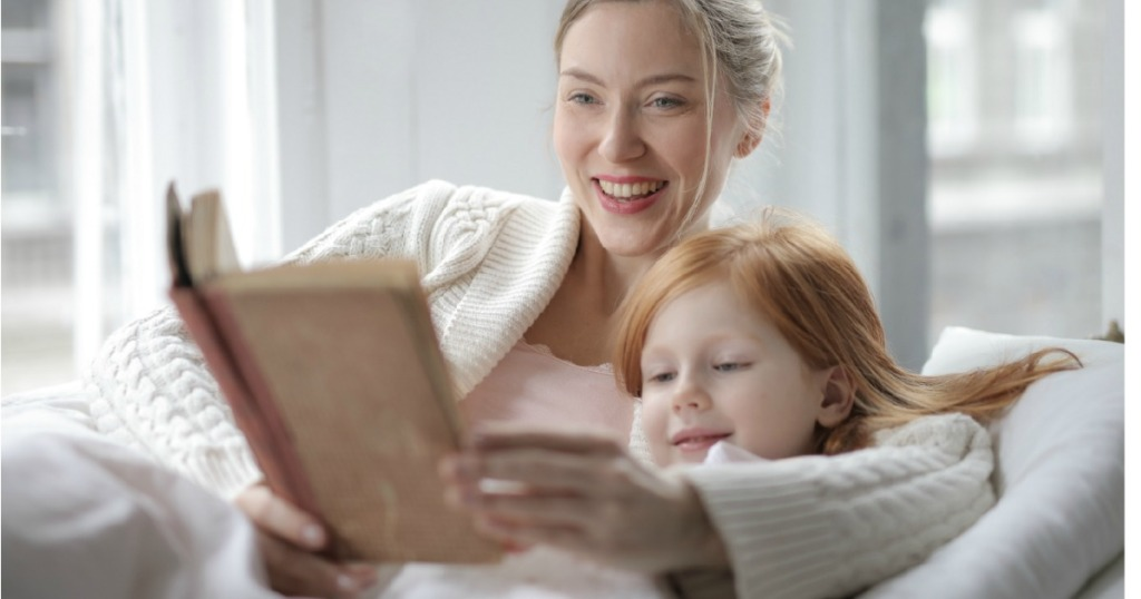 Woman reading book to child in bed