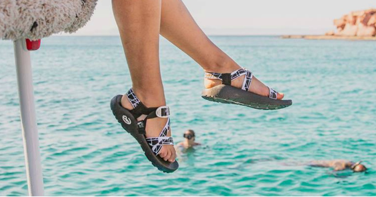 Woman dangling legs over water wearing black and white strappy sandals