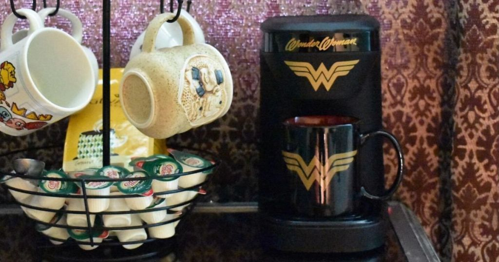 wonder woman coffee maker next to mug rack with creamers
